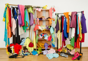 Untidy cluttered woman wardrobe with clothes and accessories.