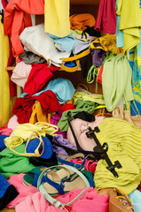 Closeup on big pile of cluttered clothes falling out of a shelf.
