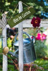 Gießkanne am Gartenzaun