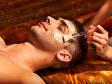 Fototapety Clay facial mask in beauty spa.