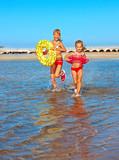 Children holding hands running on  beach.