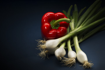 Fresh whole red bell pepper with spring onions