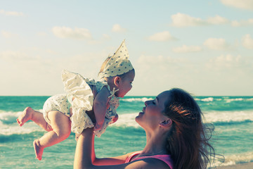 portrait of young mother and her cute baby on the seaside
