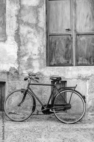 Classic bicycle leaning against a wall B&W image