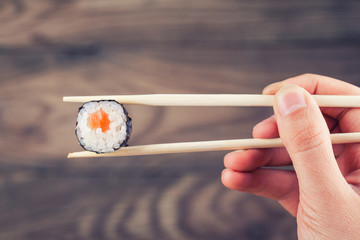 Hand holding sushi roll using chopsticks