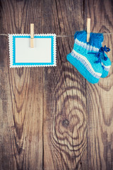 knitted baby socks and blank note hanging on clothesline against