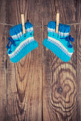 knitted baby socks hanging on clothesline against wooden backgro