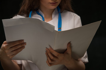 Unrecognizable doctor reading medical record