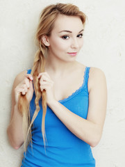 Hairstyle. Blond woman teenage girl plaiting braid hair.