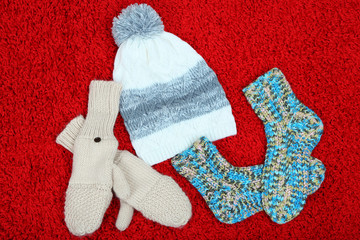 Winter cap, socks and gloves,  on color background