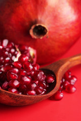 Ripe pomegranates on red background
