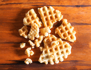 Crushed waffle on wooden background