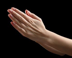 Praying human hands on black background