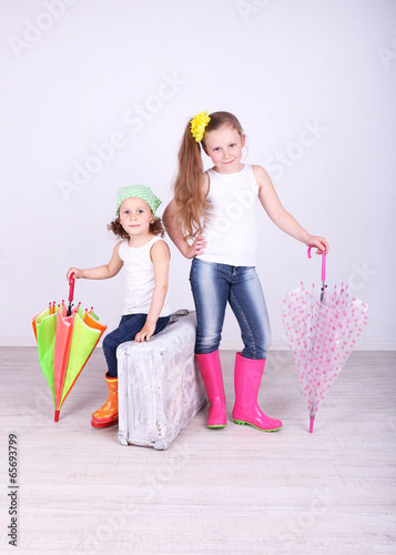 Beautiful small girls with suitcase on light background