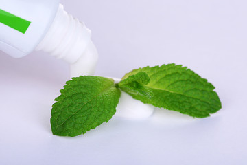 Toothpaste squeezed from tube, mint leaves, close-up, isolated