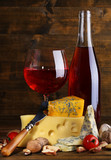 Pink wine and different kinds of cheese on wooden background