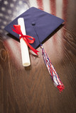 Graduation Cap, Diploma on Table with American Flag Reflection - 65694517