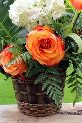 Basket of flower, rose and hydrangea on a wooden board