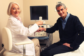 Mature female doctor examining man in 40s. Wrist and arm scan