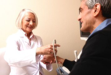 Mature female doctor scanning man in 40s. Wrist and arm exam