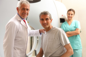 Happy senior doctor with his male patient at CT scanner machine.
