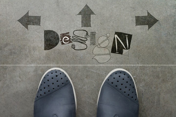 Hand drawn DESIGN design word on front of business man feet as c
