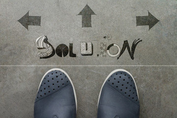 Hand drawn SOLUTION  design word on front of business man feet a