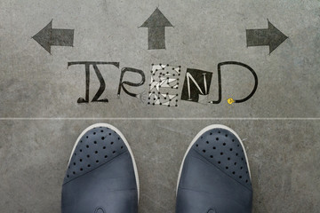 Hand drawn TREND design word on front of business man feet as co