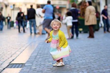 Cute little girl eating ice-cream in the center of crowed street