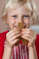 Close-up of cute boy holding up gingerbread man