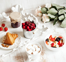 Healthy breakfast with cottage cheese, cacao, cherry and croissa