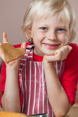 Cute boy holding up gingerbread love heart