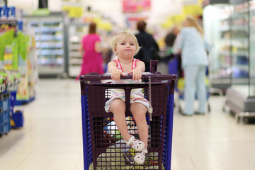 Funny little girl in shopping cart at hypermarket