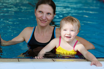 Young mother with little girl swimming in the pool