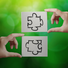 Hand holding hand drawn  Partnership Puzzle icon on cavas board