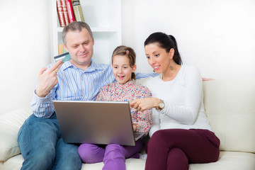 Smiling parents and little girl with laptop and credit card at h