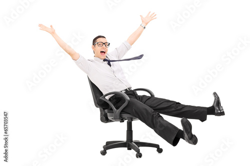Man riding in an office chair and gesturing joy