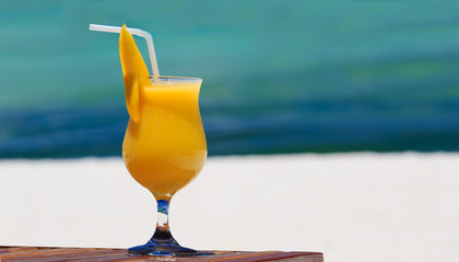 mango cocktail on tropical beach