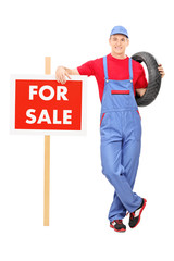 Male mechanic standing by a for sale sign