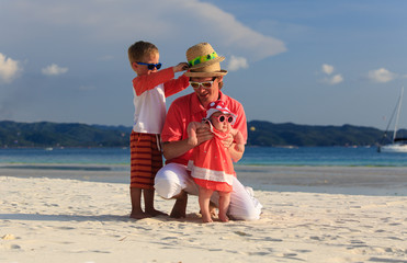 father with kids having fun on the beach