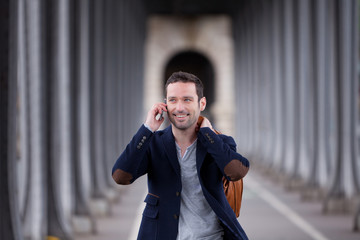 Young attractive man using smartphone in Paris