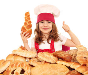 happy little girl cook with breads rolls and thumb up