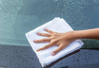 Young girl hand wiping a car glass dry