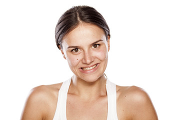 young woman without make-up with a false smile