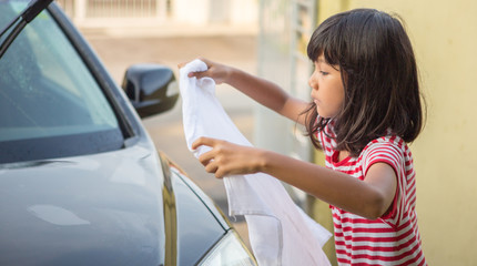 Young Asian Malay girl washing car