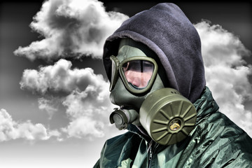 Man in a gas mask against polluted nature