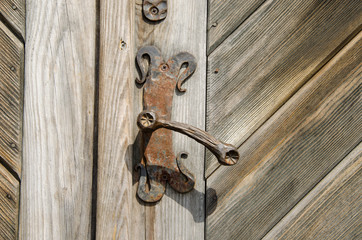 ancient manor door handle on old wooden door