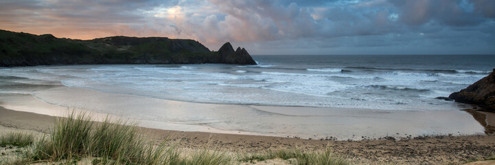 Sunrise landscape panorama Three Cliffs Bay in Wales with dramat