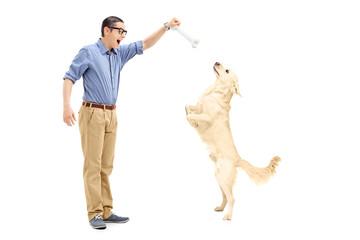 Young man luring a dog with a bone