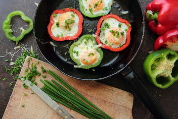 Fried eggs in colorful peppers and green chive for breakfast